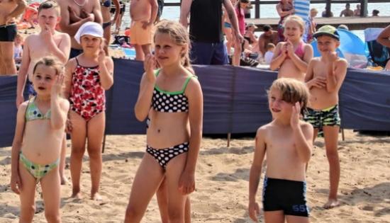 dzieci z klownem na plazy w Lginiu