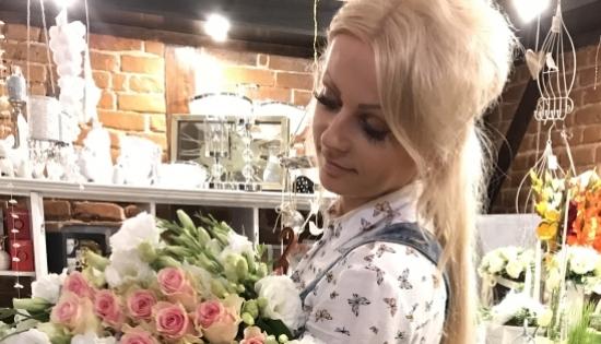 Pani Szyszka z bukietem kwiatów w swojej kwiaciarni