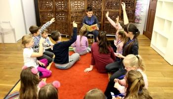 uczestnik czytajacy książkę i zgłaszające się dzieci