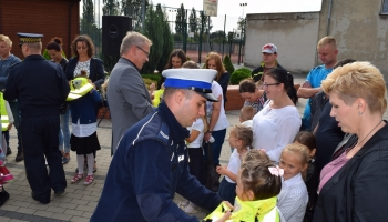 policjant zakłada kamizelkę uczniowi