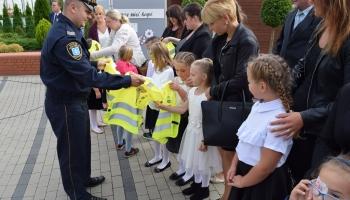 strażnik miejski zakłada kamizelkę uczniowi