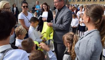 zastępca burmistrza wręcza kamizelki odblaskowe pierwszoklasistom