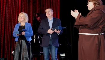 prezes spółki komunalnej, zastępca burmistrza i franciszanin na scenie wręczają nagrody