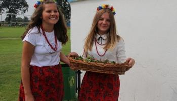 dwie dziewczyny w stroju ludowym witające gości