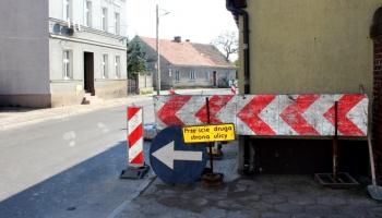 remontowany chodnik oraz znaki z informacją o przejściu drugą stroną ulicy