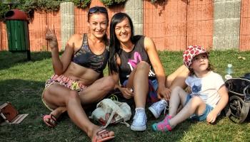 dwie dziewczyny z dzieckiem siedzące na trawie