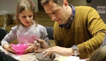 dziewczynka z tatą wykonuje pracę z gliny