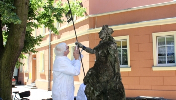 dwie osoby odnawiają rzeźbę