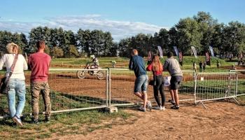 widzowie przy barierkach oglądający wyścigi