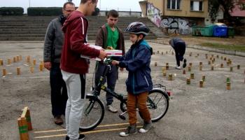 dzieci jeżdżące rowerem na placu manewrowym