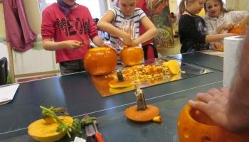 dzieci rzeźbiące w dyniach