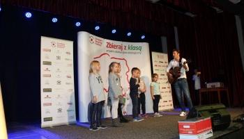 Mariusz Totoszko grający na gitarze z dziećmi