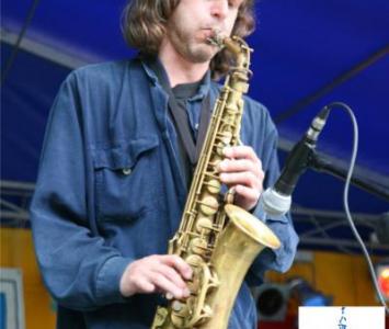 mężczyzna w niebieskiej koszulu grający na saksofonie