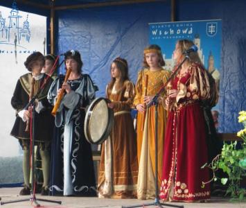 grupa młodych kobiet przebrana w średniowieczne stroje grająca na instrumentach