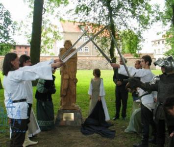 grupa przebranych młodych ludzi krzyżuje nad głowami miecze obok drewnianego pomnika