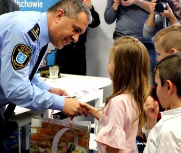 komndant straży wręcza nagrody dzieciom