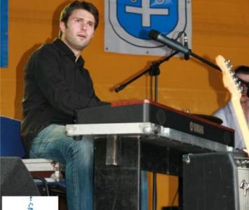 mężczyzna siedzący na scenie przy organach