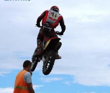 motocyklista podczas wyskoku na enduro obok męzczyzna z obsługi