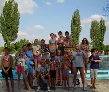 grupa dzieci wraz z dorosłymi pozująca z medalami do zdjęcia na tle basenu 1
