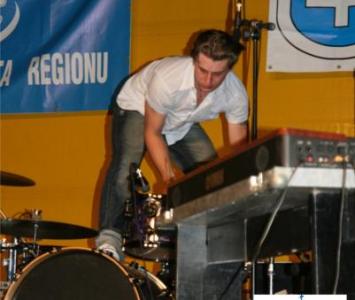 mężczyzna w białej koszuli stojący obok perkusji