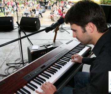mężczyzna gra na keybordzie i śpiewa do mikrofonu