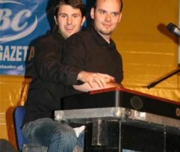 dwójka mężczyzna siedząca na scenie przy organach