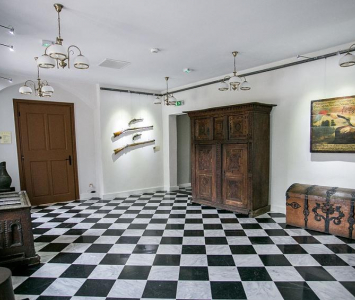 pokój z zabytkowymi meblami oraz biało czarnymi kaflami na podłodze