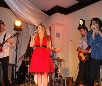 zespoł podczas konceru z wokalistką w czerwonej sukience 1