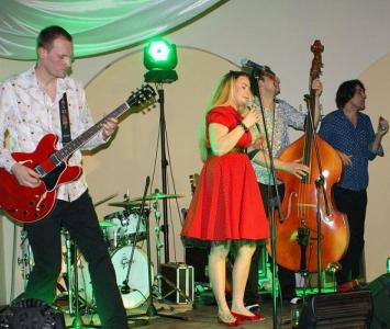 zespoł podczas konceru z wokalistką w czerwonej sukience 2