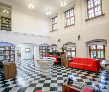 sala z biało czarnymi kafelkami na podłodze i czerwonymi kanapami