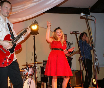 zespoł podczas konceru z wokalistką w czerwonej sukience 3